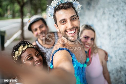 Happy friends taking selfie at a carnival party in Brazil