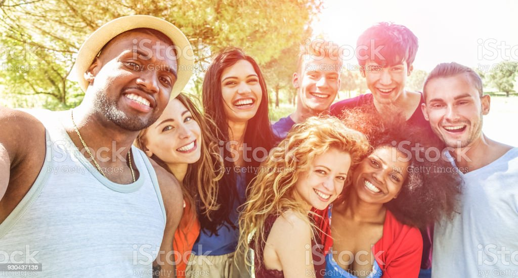 Happy friends taking selfie at bbq picnic in nature park with back sunlight - Young people having fun with trends technology - Youth lifestyle, tech and friendship concept - Focus on african man face stock photo