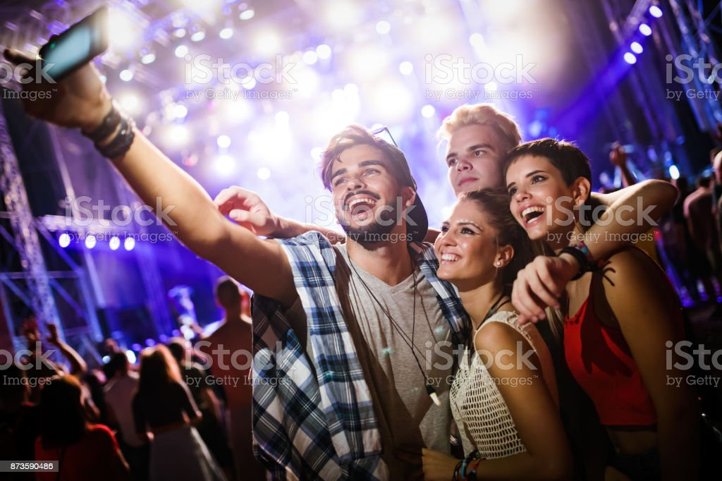 Happy friends taking selfie at music festival royalty-free stock photo