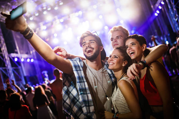 happy friends taking selfie at music festival - parties stock photos and pictures