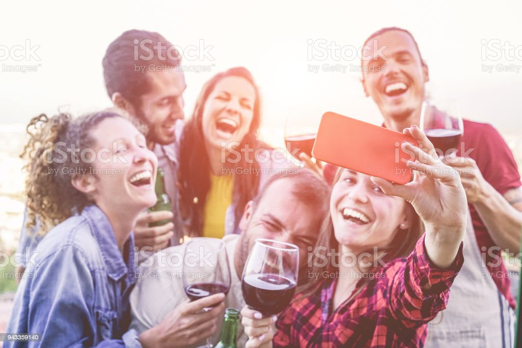 Happy friends taking selfie during party dinner at home backyard -...