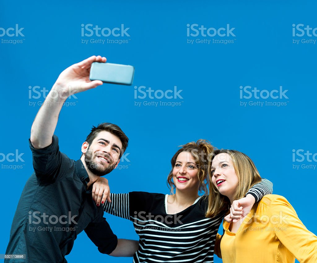 Happy friends taking selfie from mobile phone against blue screen stock photo