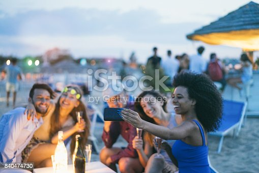 Happy friends taking selfie with smartphone at beach party outdoor - Young people having fun together at kiosk bar drinking champagne  - Focus on african girl hand phone- Youth and summer concept