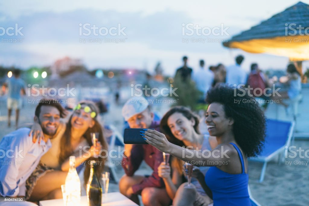 Happy friends taking selfie with smartphone at beach party outdoor - Young people having fun together at kiosk bar drinking champagne  - Focus on african girl hand phone- Youth and summer concept stock photo