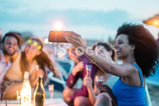 istock Happy friends taking selfie with smartphone at beach party outdoor - Young people having fun at kiosk bar drinking champagne - Soft focus on mobile cell phone - Youth lifestyle and vacation concept 922130050
