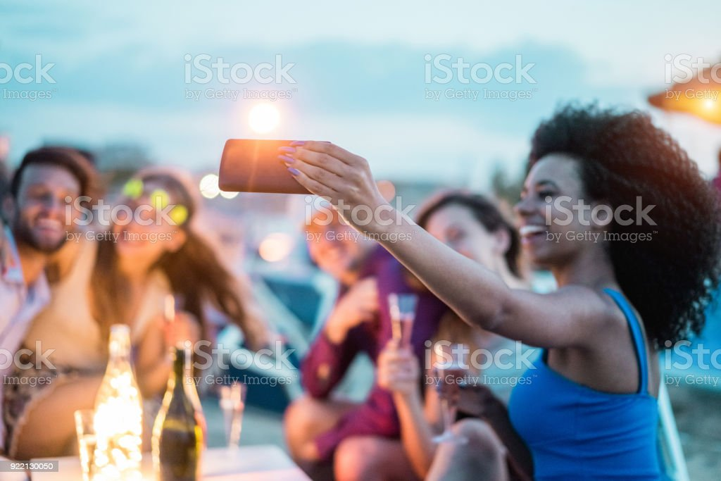 Happy friends taking selfie with smartphone at beach party outdoor - Young people having fun at kiosk bar drinking champagne - Soft focus on mobile cell phone - Youth lifestyle and vacation concept stock photo