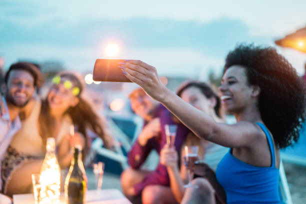 happy friends taking selfie with smartphone at beach party outdoor - young people having fun at kiosk bar drinking champagne - soft focus on mobile cell phone - youth lifestyle and vacation concept - holiday event stock pictures, royalty-free photos & images