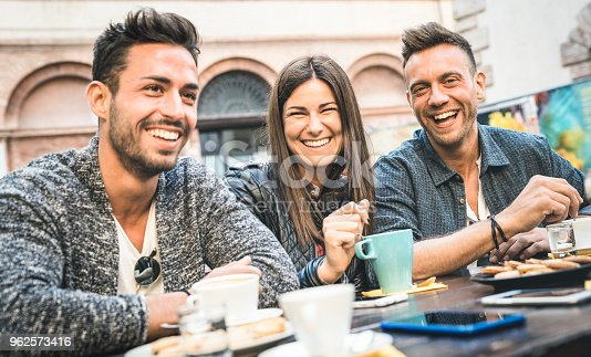 istock Happy friends talking and having fun at pub restaurant drinking cappuccino and hot tea - Young people together at fashion cafeteria - Friendship concept with men and women at coffee bar - Cold filter 962573416