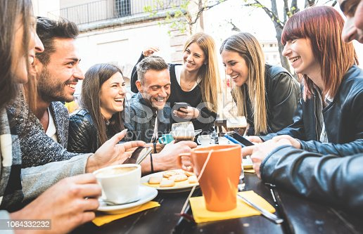 istock Happy friends talking and having fun with mobile smart phones at restaurant drinking cappuccino and hot tea - Young people together at cafeteria - Friendship concept with men and women at coffee bar 1064332232