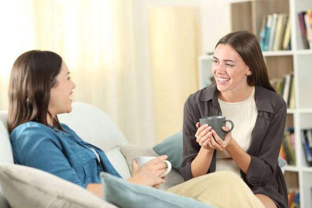 amigos felices hablando en casa en un sofá - happy couple sharing a cup of coffee fotografías e imágenes de stock