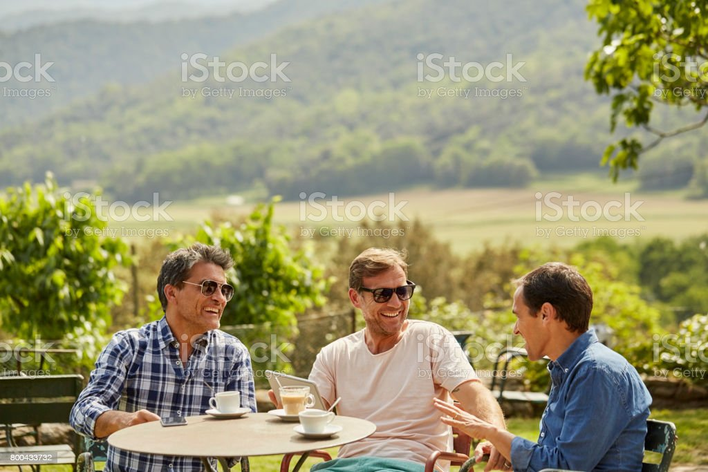 Happy friends talking while having tea in yard stock photo