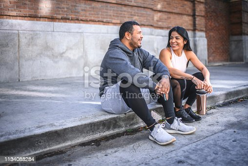 Cheerful male and female friends talking while sitting on sidewalk. Athletes are in sportswear. They are against brick wall.