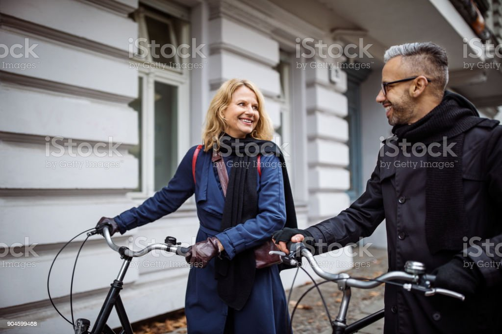 Happy friends talking while walking with bicycles royalty-free stock photo