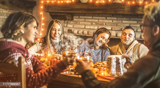 1064325668 istock photo Happy friends tasting christmas sweet food at home fun party - New year's eve mood with white wine glasses toast - Winter holiday concept with young people eating together - Bulb lights warm filter 1177263357