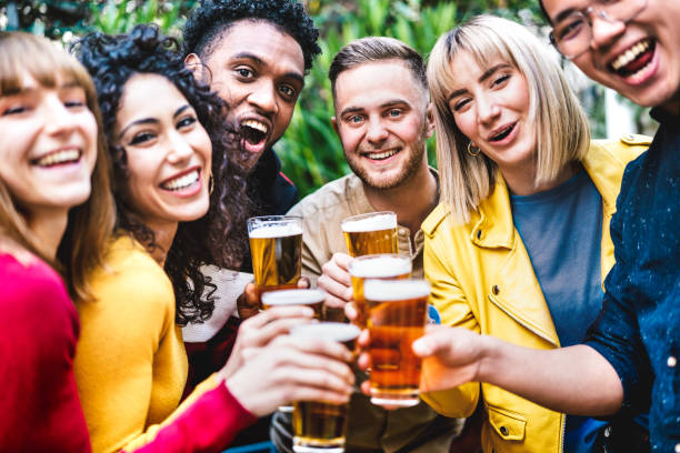 Happy friends toasting beer at brewery bar dehor - Friendship life style concept with young millennial people enjoying time together at open air pub - Warm vivid filter with focus on central guy stock photo