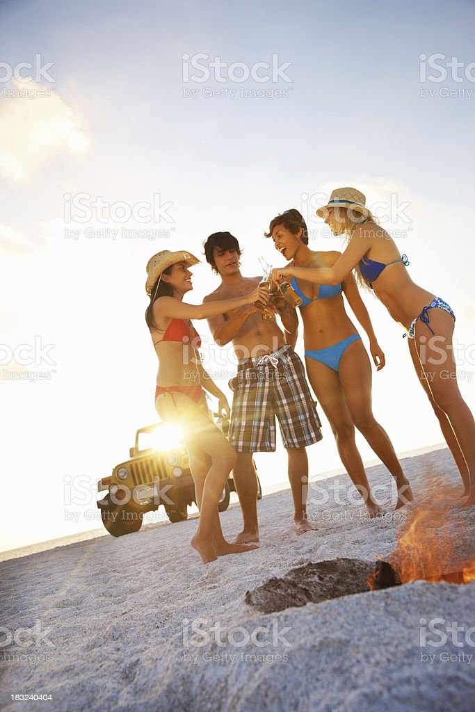 Happy friends toasting beer by bonfire with jeep in background royalty-free stock photo