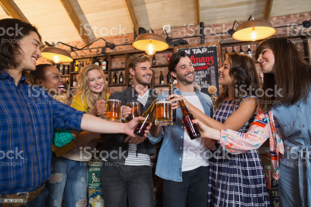 Happy friends toasting beer glasses and bottles in pub royalty-free stock photo