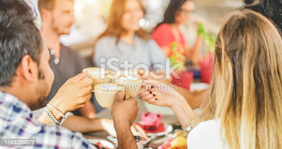 istock Happy friends toasting with cappuccino at bar cafe - Young trendy people enjoying breakfast - Friendship, youth lifestyle and meal break concept - Focus on bottom indian man hand 1143250077