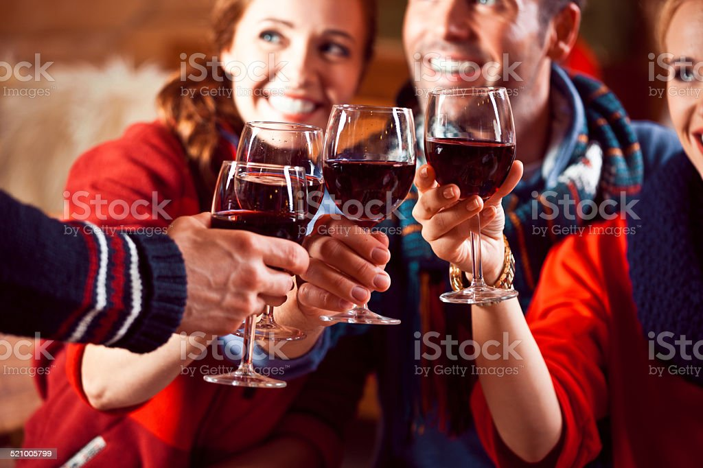 Happy friends toasting with wine in the evening Group of friends wearing warm clothes toasting with red wine int he restaurant in the evening. Focus on wine glasses. Adult Stock Photo