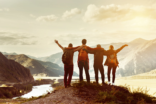 Four happy friends are looking on mountains and having fun together. Space for text. Travel concept