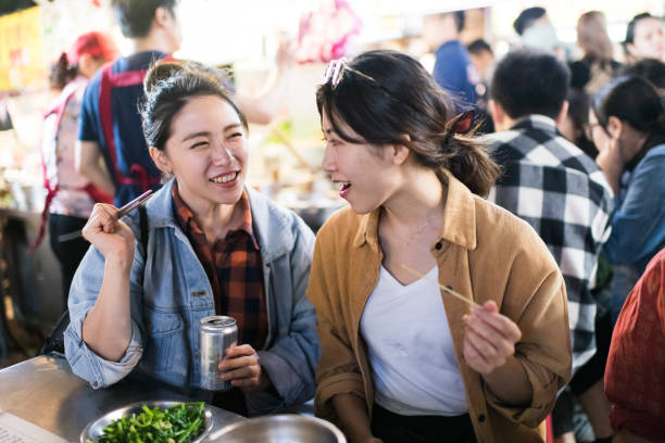 Happy friends trying new foods at night market stock photo