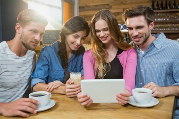 glückliche freunde mit digital-tablette bei kaffee - schwarzer kaffee net stock-fotos und bilder