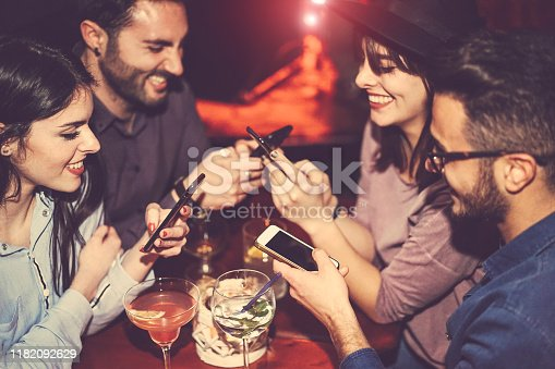 istock Happy friends using mobile phone and having fun with cocktails in a jazz bar - Young people addicted to new smartphone technology - Concept of youth, cellphone and lifestyle - Focus on right male hand 1182092629