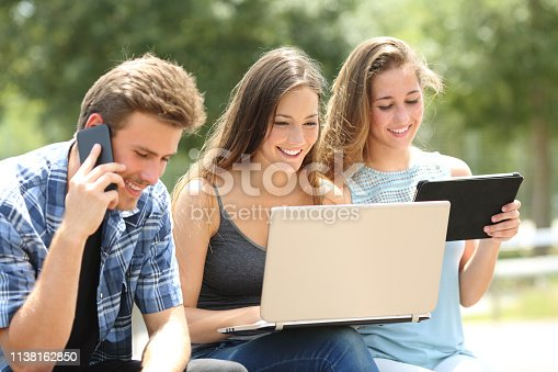 istock Happy friends using multiple devices on a bench 1138162850