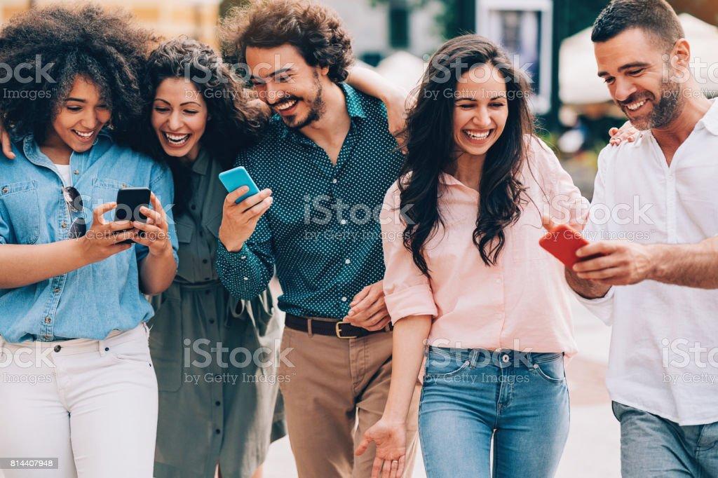 Amigos felizes usando telefones inteligentes - foto de acervo