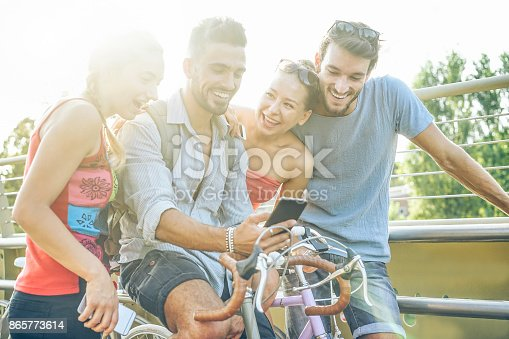 istock Happy friends using smartphone for watching videos outdoor - Young people sharing media in new social network - Youth and technology trends concept - Main focus on right woman face - Warm filter 865773614