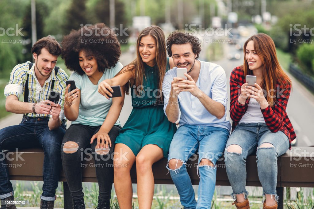 Happy friends using smartphones Group of friends sitting on the bridge and using smartphones 20-29 Years Stock Photo