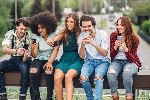 Happy Friends Using Smartphones Stock Photo - Download Image Now