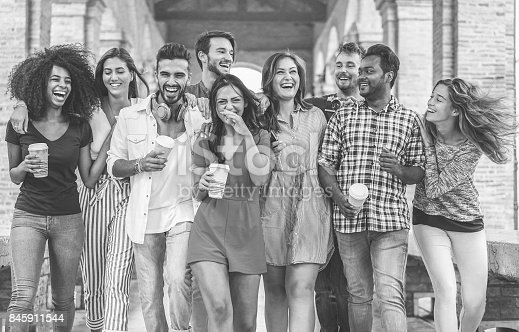 istock Happy friends walking in city center with coffee paper cup - Diverse culture students having fun together  - Youth, friendship, and bonding concept - Main focus on center three guys - Vintage filter 845911544