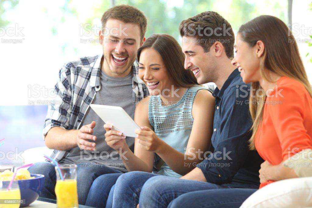 Happy friends watching media in a tablet - foto de acervo
