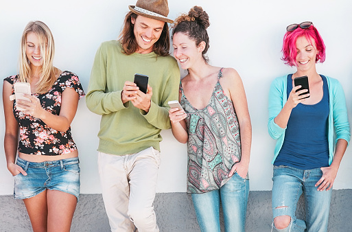 Happy friends watching on their smart mobile phones outdoor - Young generation having fun with new technology and social network - Concept of millennials people, tech and youth addiction lifestyle