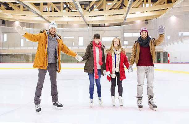 happy friends waving hands on skating rink people, friendship, gesture, sport and leisure concept - happy friends waving hands on skating rink ice rink stock pictures, royalty-free photos & images