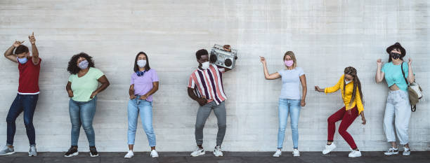 happy friends wearing face mask listening music with vintage boombox outdoor - multiracial young people having fun dancing together during corona virus outbreak - youth millennial friendship concept - afro latino mask imagens e fotografias de stock
