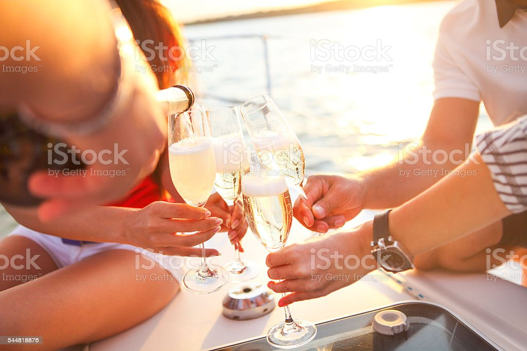 Happy friends with glasses of champagne on yacht. Vacation, trav - foto de stock