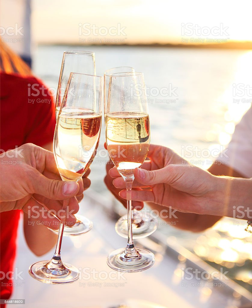 Happy friends with glasses of champagne on yacht. Vacation, trav stock photo