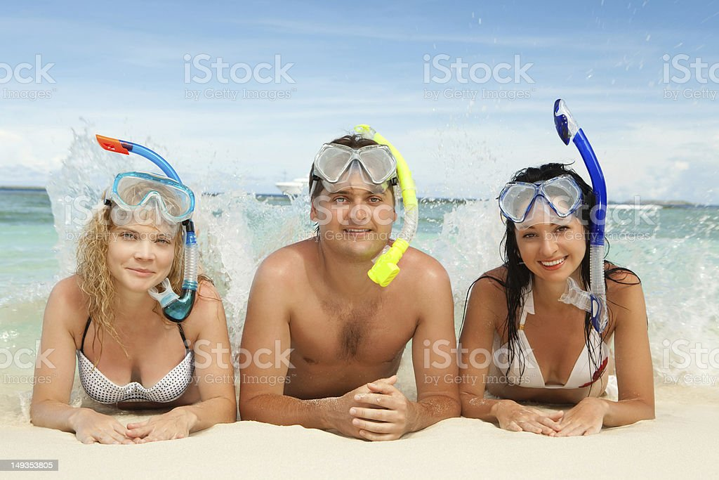 Happy friends with snorkeling equipment on the beach stock photo
