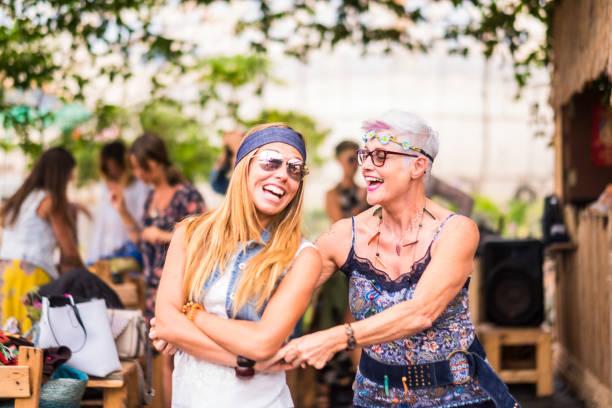 glückliche freundschaft paar frau junge und reife damen mit hippie kleidung und kleid haben spaß zusammen tanzen und umarmen einander. schöne erwachsene genießen eine farbige festival - hippie kleider stock-fotos und bilder
