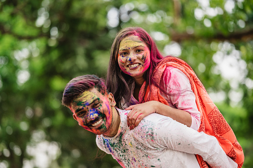 Happy fun loving Asian Indian couple painted in colors or gulal celebrating holi festival