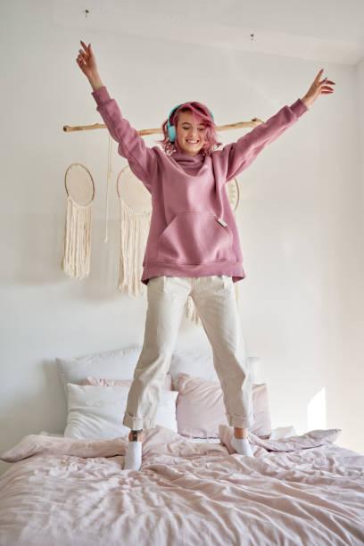 幸せなファンキーな十代の女の子ピンクの髪の着用ヘッドフォンは、ベッドの上で音楽ジャンプダンスを聴きます。 - gen z ストックフォトと画像
