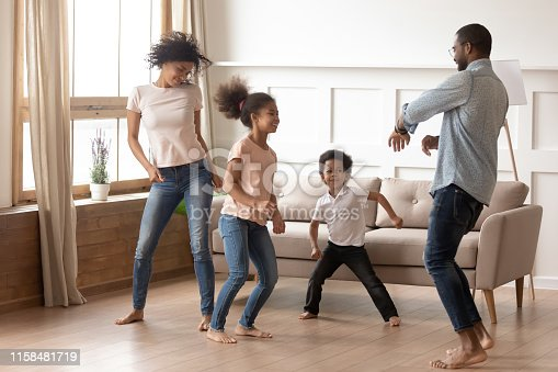 Happy funny active african american family of four parents and cute little mixed race kids dancing laughing in living room, black mom dad with small children having fun together enjoy leisure at home