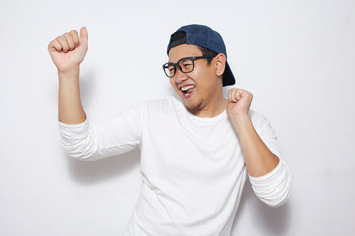 Photo image closeup portrait of a funny young Asian man dancing happily joyful expressing celebrating good news victory winning success gesture, smiling positive excited emotion while standing over white background