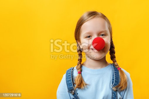 Happy funny child clown with a red nose. Cheerful little girl on a yellow background. April 1st Fool's Day. Copy space.
