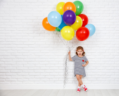 Happy funny child girl with  colorful balloons near an brick wall