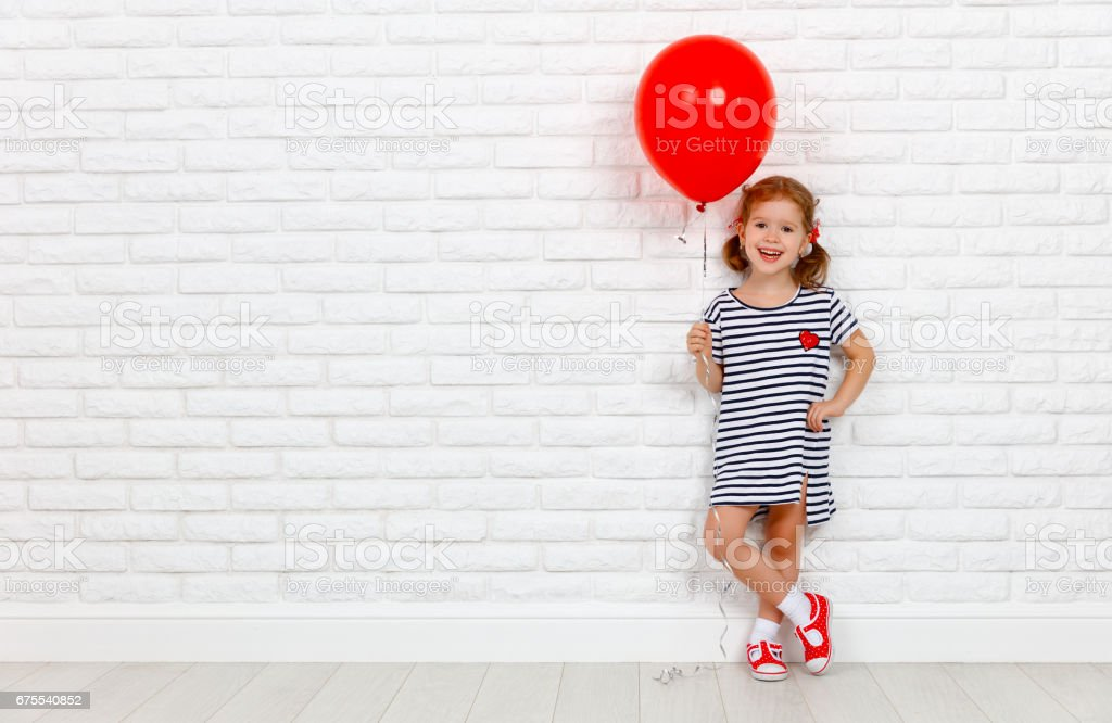 Happy funny child girl with  red ball near an brick wall stock photo