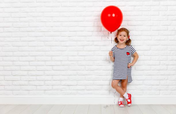 glücklich lustige kind mädchen mit roten ball in der nähe einer ziegelwand - kinderparty spiele stock-fotos und bilder