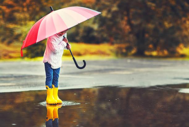 glückliches kind lustig mädchen mit regenschirm springen auf pfützen in gummistiefeln - mädchen dusche stock-fotos und bilder